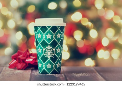 Dallas, TX - November 5, 2018: Starbucks popular holiday beverage, served in the new 2018 designed holiday cup. Festive holiday Christmas lights background.