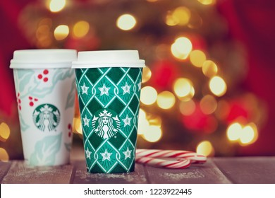 Dallas, TX - November 5, 2018: Starbucks popular holiday beverage, served in the new 2018 designed holiday cups. Displayed on rustic table with candy canes. Festive Christmas lights background.
