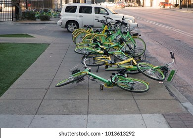 Dallas, TX / USA 1-30-2018 Ride share bikes can clog sidewalks causing concerns for pedestrians. Sometimes they end up in a tangled mess when the wind blows them over. Lime and OFO bikes shown.