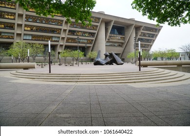 """Dallas, TX / USA - 4/3/2018 - Dallas City Hall is shown from the far side of the plaza with the """"The Dallas Piece"""" a statue designed by Henry Moore."""