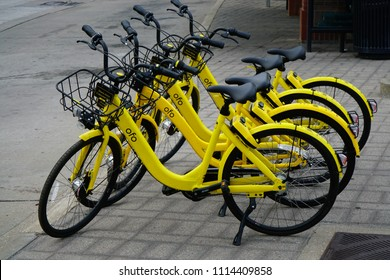 Dallas, TX / USA 6/12/2018 –OFO bikes are lined up on the sidewalk ready for a rider to unlock one and go.