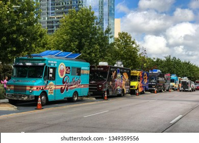 Dallas, TX / USA - October 6, 2018:  Several colorful food trucks are parked all in a row on a street beside a public park on a Saturday on October 6, 2018 in Dallas, TX.