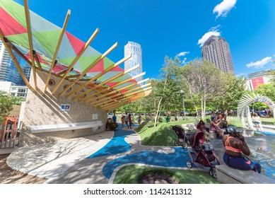DALLAS, TX, USA-JUL 14, 2018:Artificial turf berm, crawl tunnel at children area in Klyde Warren Park. A 5.2-acre public place in downtown Dallas. Water fountain, splash pad concrete seating, boulders