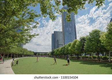 DALLAS, TX, USA-MAY 26, 2018:Klyde Warren Park, a 5.2-acre public park in downtown Dallas, Texas. People playing sport on green lawn grass under sunny day cloud blue sky. Live oak tree and skyscraper