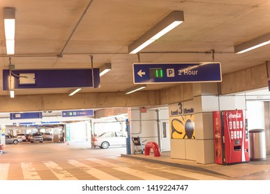 DALLAS, TX, US-MAY 16, 2019: 2 hour parking overhead neon sign at indoor American airport parking lot displays number of available parking spaces. Available empty spots display counter information