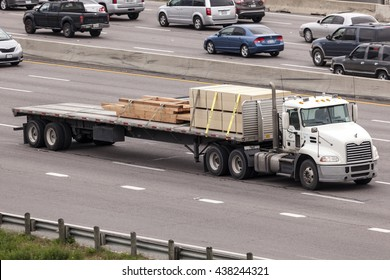 DALLAS, USA - APR 8, 2016: Flatbed semitrailer freight truck on the highway in United States
