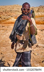 Dallol, Ethiopia - January 03, 2019: Guard with rifle posing among sulfur deposits in the desert of Dallol, Ethiopia.