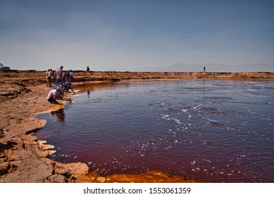 Dallol, Ethiopia - January 03, 2019: Tourists watching the Yellow Lake water, intensely colored in orange, surrounded by desert rocks in Dallol, Ethiopia.