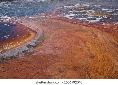 Dallol, Ethiopia - January 03, 2019: Yellow Lake with water, being intensely colored in orange, surrounded by desert rocks in Dallol, Ethiopia.