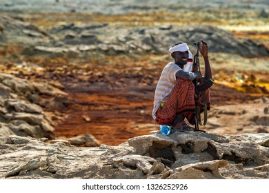 Dallol/Ethiopia-02/02/2019: Man from afar tribe with his rifle on background of Dallol volcano