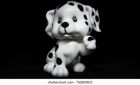 Dalmatian puppy ceramic statue on black background, happy mood