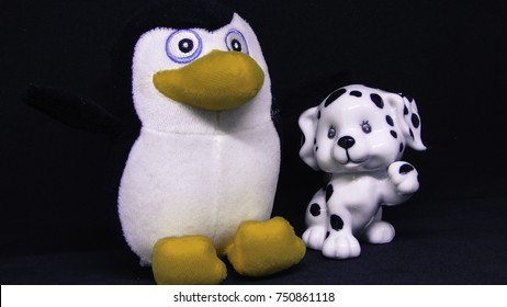 Dalmatian puppy ceramic statue and penguin toy on black background