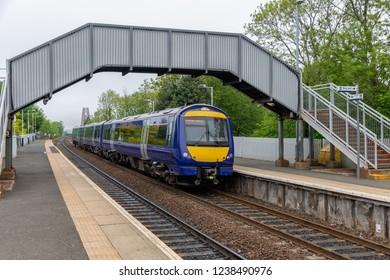 Dalmeny station with train near Forth railway Bridge over Firth of Forth, Scotland
