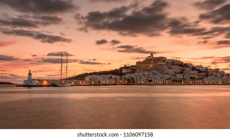 Dalt vila old town and Ibiza harbour at sunset , skyline with cloudy sky.