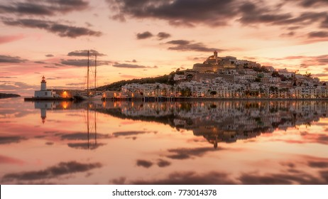 Dalt vila old town and Ibiza harbour at sunset , skyline reflection .