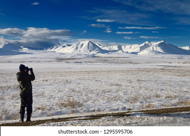Dalton Highway, Alaska, United States - October 14, 2013: Female tourist taking a picture of snow covered Brooks Range mountains from the Dalton Highway Alaska with model release