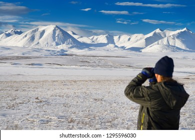 Dalton Highway, Alaska, United States - October 14, 2013: Female tourist looking at the snow covered Brooks Range mountains with binoculars from the Dalton Highway Alaska with model release