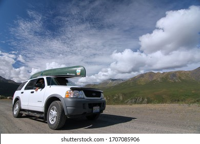 Dalton Highway, Yukon, Canada. 8/21/2016. Ford explorer transporting a canoe with mountain range in the background.