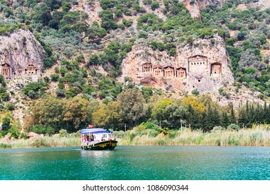 DALYAN, TURKEY - 16 APRIL 2018:  River boat with tourists on the river Dalyan by the sheer cliffs with the weathered facades of Lycian tombs cut from rock, circa 400 BC.