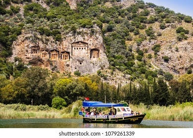 DALYAN, TURKEY - APRIL 16, 2018:  Small boat with tourists on the river Dalyan visiting ancient Lycian tombs cut from rock, circa 400 BC.