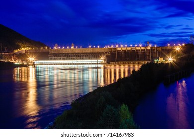 The dam of hydroelectric power station in twilight lit with lamps, night, the picture on long endurance