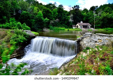 The dam at Oak Creek Pond with a park building in the background on a beautiful summer weekday.  The long exposure gives the waterfall a cottonlike appearance.  The park is in South Milwaukee.