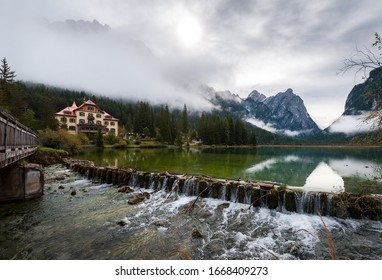 Dam on Lake Toblach with hotel during cloudy weather and fog