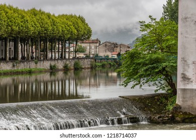 Dam on the river Salat in the village of Saint Girons and in the background you can see the Pyrenees. France