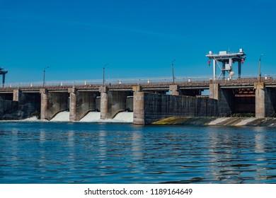 Dam water release into river. Water rushing through gates.