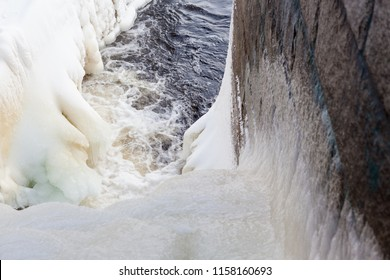 Dam at winter flowing water and ice formations