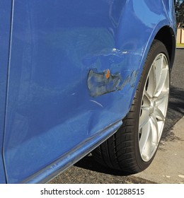 Damage on blue car door with bending, scratches and damaged paint after light road accident needs body repair, alloy wheel and asphalt in corner