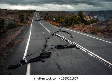 Damaged asphalt road (Crater Rim Drive) im Hawaii Volcanoes Nationalpark nach dem Erdbeben und dem Ausbruch des Kilauea (Rauch oben rechts) im Mai 2018. Große Insel, Hawaii