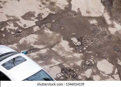 Damaged asphalt road with potholes