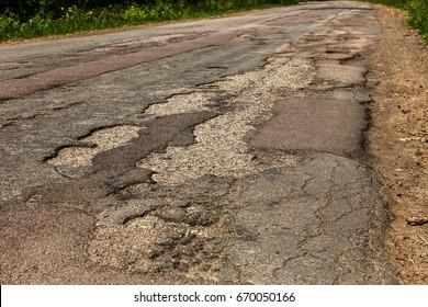Damaged asphalt road with potholes. Bad road.  Bad asphalt,  Broken automobile road, cracks, holes, potholes in asphalt