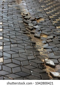 Damaged asphalt road with potholes, caused by freeze-thaw cycles in winter. Bad road. Broken pavements sidewalks on sidewalk. pavement with paving slabs with defects and cracks coming in perspective