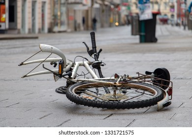The damaged bicycle lying on the street in the city center. The demolished bicycle as street art - performance, Linz, Austria.