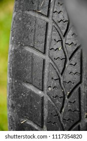 Damaged black tire of a large car. Old tires, detail of old and worn wheels, wheels to pull. Deflated Flat tire on road stranded in danger.Old car worn tire with a worn tread. Close up of old tire