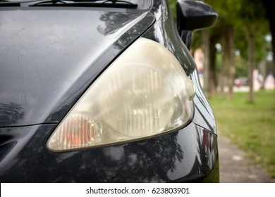 Damaged and blurred headlight surface as a result of weather condition and aging of a car