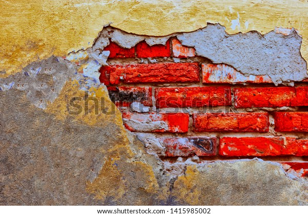 Damaged brick wall with worn weathered plaster