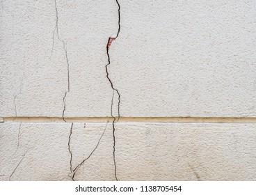 Damaged broken building facade, fissured surfaces of concrete