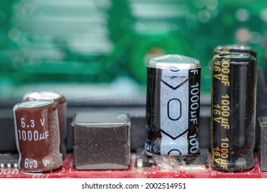 Damaged capacitor on a circuit board. Top is bulged out showing failure. Undamaged capacitors also present. No brand markings. Shallow depth of field.