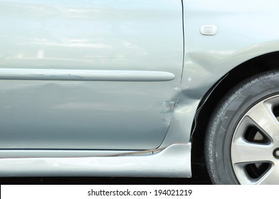 Damaged car with a dent near the wheel - can be considered as a fender bender