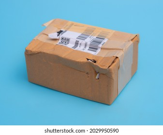 Damaged cardboard box with hole on blue background,cardboard box destroyed in shipping
