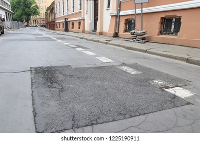 Damaged city street - cracks and patches on blacktop. Wroclaw, Poland.