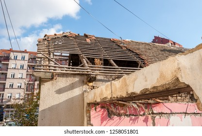 Damaged and collapsed roof tiles after aftermath earthquake or hurricane on the old ruined domestic house with broken windows selective focus