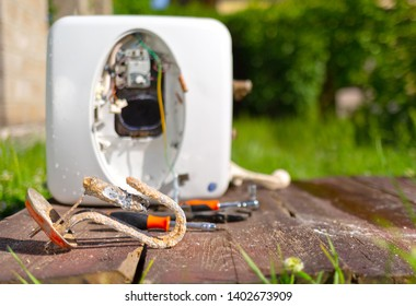 Damaged from corrosion and rust, the water heater lies on the background of the boiler on a wooden table.