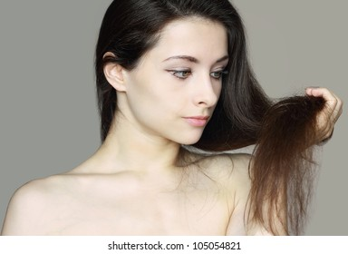 Damaged dry woman hair. Closeup portrait of woman holding hand long hair and thinking unhappy