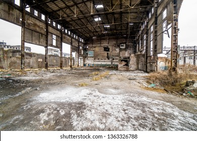 Damaged factory inside with many holes and ruined roof. Old factory background building after earthquake disaster or war.