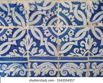 Damaged, faded, not corrected vintage azulejos, glazed ceramic tiles with painted blue white ornaments. Heritage Concept of traditional Portuguese art. Decorative old background for design or backdrop