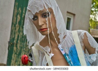 damaged female display dummy that is wearing a torn and used disposable painters suit in front of a house with a vintage green door